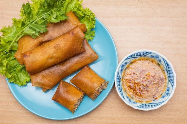 Smażone dim sum na niebieskim talerzu i warzywach
