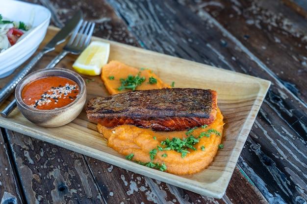 Smażone filety z łososia podawane z dodatkami warzywnymi na drewnianym talerzu i sosem, z bliska. pieczony filet z łososia ze słodkimi puree ziemniaczanym.
