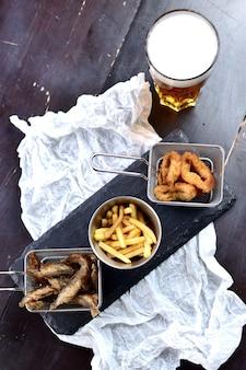Smażone frytki, smażona ryba i krążki cebuli w cieście na drewnianej desce, przy szklance piwa. przekąski do piwa