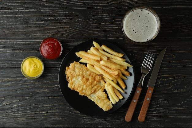 Smażone frytki z rybą i piwem na podłoże drewniane