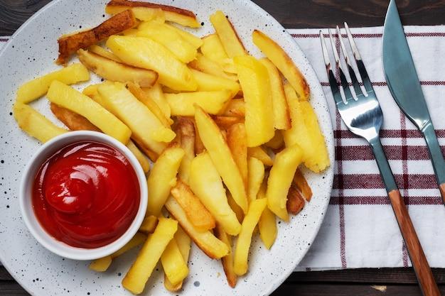 Smażone frytki ziemniaczane z pomidorowym sosem keczupowym na talerzu. drewniany stół. skopiuj miejsce