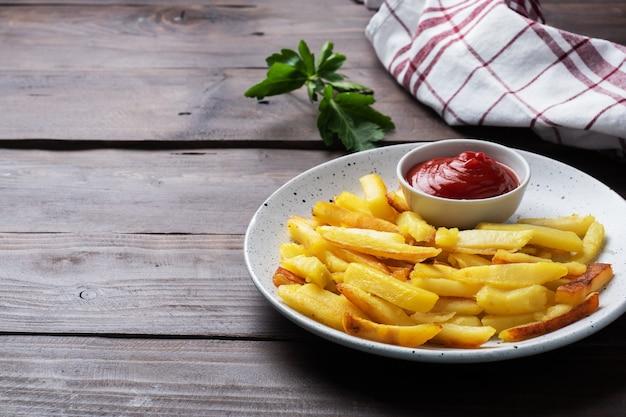 Smażone frytki ziemniaki z sosem pomidorowym ketchupem na talerzu.