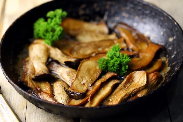 Smażone grzyby eringi na patelni na drewnianej powierzchni