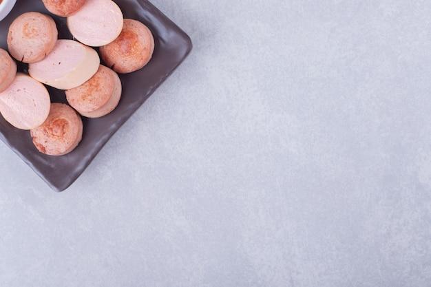 Smażone i gotowane smaczne kiełbaski na ciemnym talerzu.