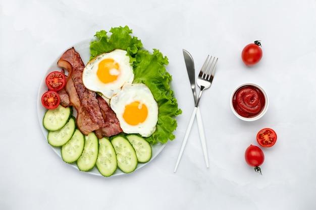 Smażone jajka kurze z boczkiem i warzywami na szarym stole. koncepcja śniadanie. widok z góry. płaska kompozycja świecka. tło żywności w godzinach porannych. świeże ogórki i pomidory w plasterkach.
