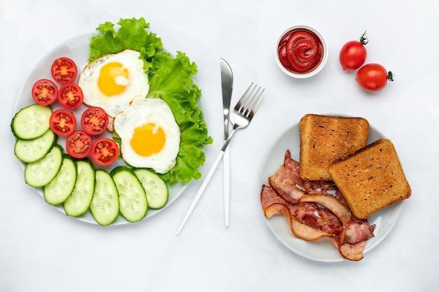 Smażone jajka kurze z boczkiem i warzywami na szarym stole. koncepcja śniadanie. widok z góry. płaska kompozycja świecka. tło żywności w godzinach porannych. świeże ogórki pokrojone w plastry i pomidory z grzanką.