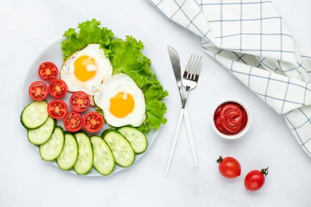 Smażone jajka kurze z warzywami na szarym stole. koncepcja śniadanie. widok z góry. płaska kompozycja świecka. tło żywności w godzinach porannych. świeże ogórki i pomidory w plasterkach.