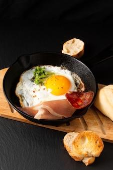 Smażone jajko na patelni żelaza patelni z kiełkami lnu i boczkiem z miejsca na kopię