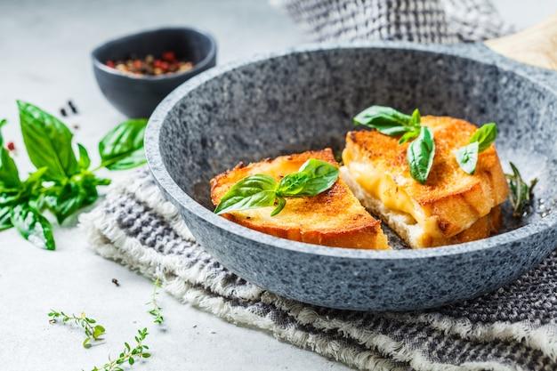 Smażone kanapki z serem i chlebem pszennym na patelni.
