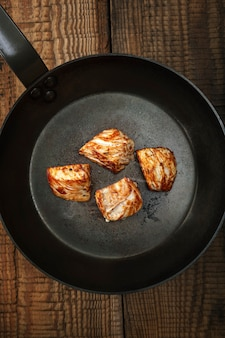 Smażone kawałki białego mięsa z indyka na stalowej patelni na starym drewnianym stole. ciemne tło.