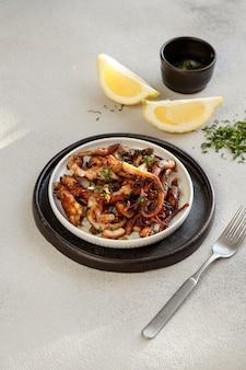 Smażone kawałki ośmiornicy z cytryną, pulpo frito, surowym bezpośrednim światłem słonecznym