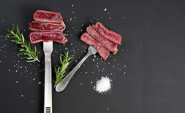 Smażone kawałki wołowiny na żelaznym widelcu na czarnym tle. stopień gotowości jest rzadki. widok z góry, skopiuj przestrzeń