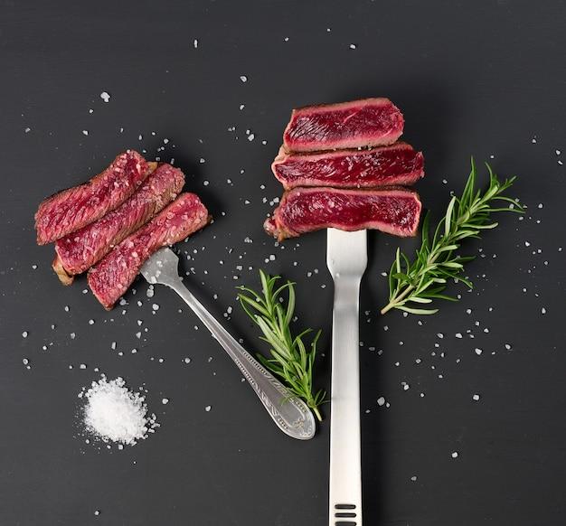 Smażone kawałki wołowiny na żelaznym widelcu na czarnym tle. stopień gotowości jest rzadki. widok z góry