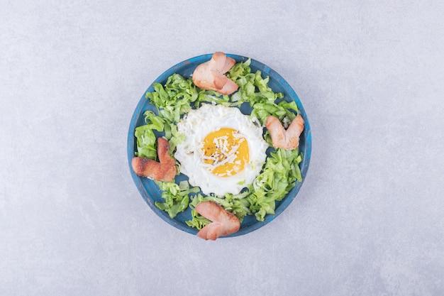 Smażone kiełbaski i jajko na niebieskim talerzu.