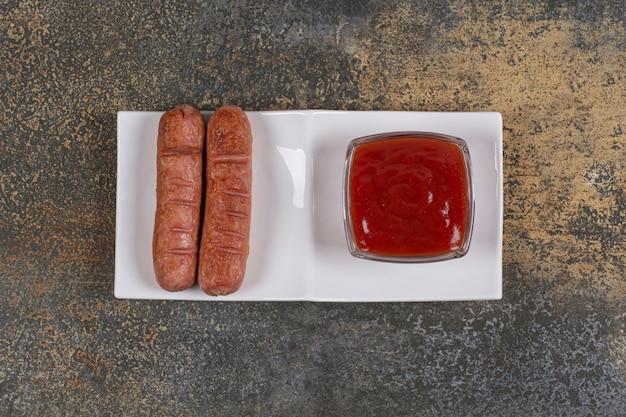 Smażone kiełbaski i keczup na białym talerzu.