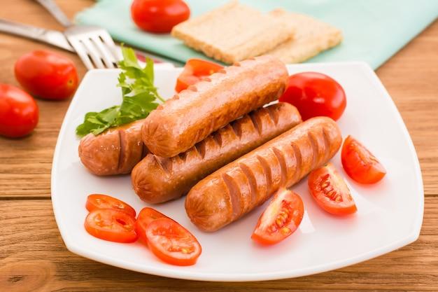 Smażone kiełbaski i pomidory na talerzu