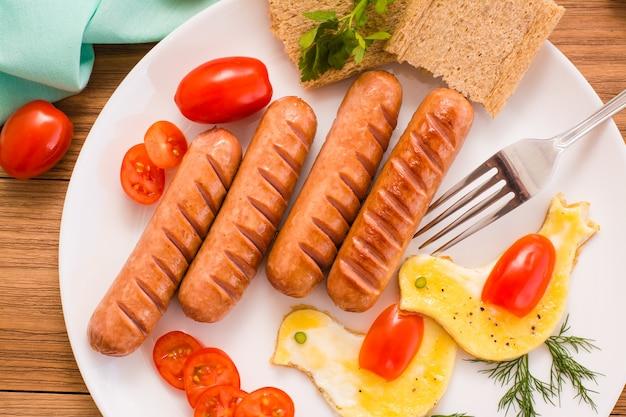 Smażone kiełbaski, jajecznica, pomidory koktajlowe i chleb, widok z góry