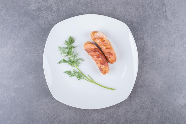 Smażone kiełbaski na białym talerzu