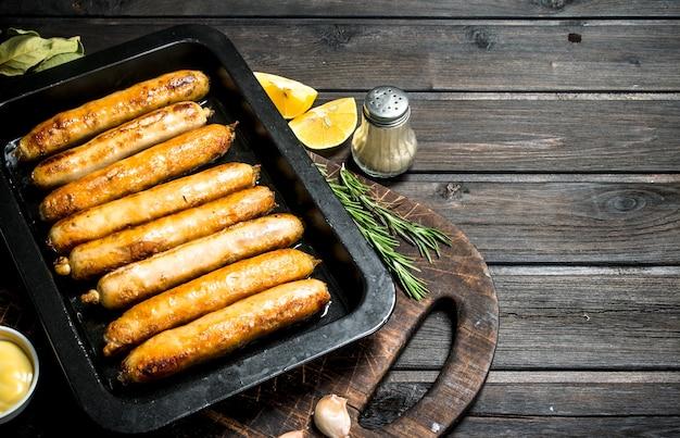 Smażone kiełbaski na blasze do pieczenia na rustykalnym stole.