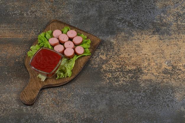 Smażone kiełbaski w plasterkach i keczup na desce.