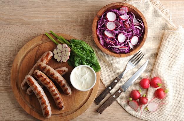 Smażone kiełbaski z grilla z sosem śmietanowym i surówką rzodkiewki z czerwoną kapustą