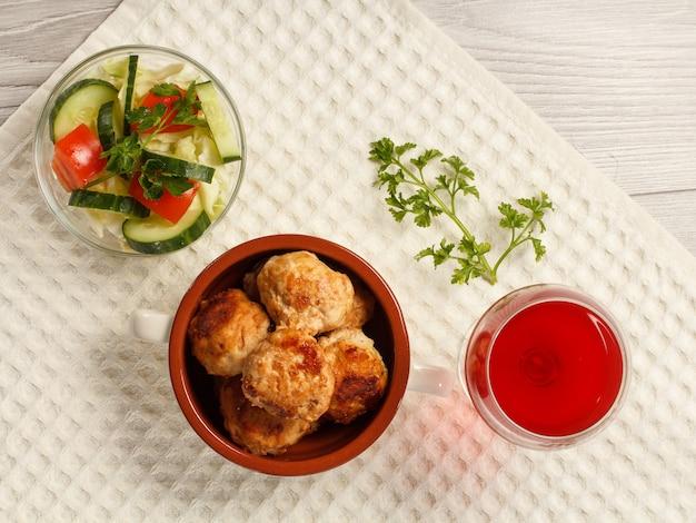 Smażone kotlety mięsne w ceramicznej misce do zupy, sałatka z pomidorów i ogórków oraz kieliszek czerwonego wina na ręczniku kuchennym. widok z góry
