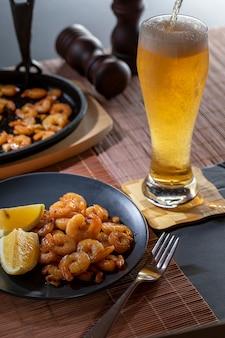 Smażone krewetki i cytryna w czarnym talerzu ze szklanką piwa