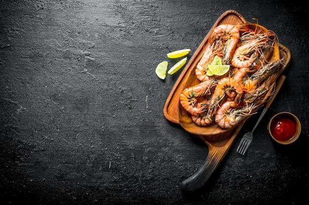 Smażone krewetki na desce do krojenia z plasterkami limonki i sosu pomidorowego na czarnym rustykalnym stole