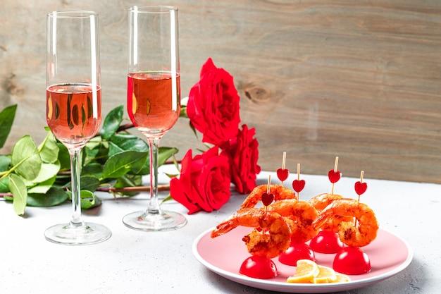 Smażone krewetki, róże i szampan na stole. oryginalne jedzenie na walentynki, romantyczna kolacja.