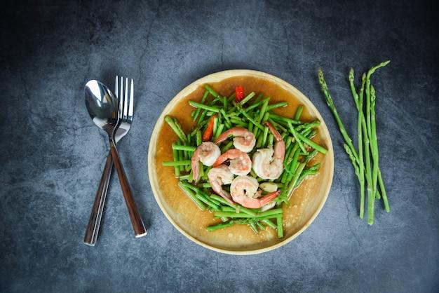 Smażone krewetki szparagowe krewetki gotowanie żywności na drewnianym talerzu i przyprawy zioła świeże szparagi wiązka na stole