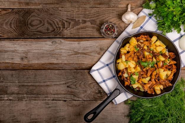 Smażone kurki z ziemniakami, cebulą i natką pietruszki na patelni i składnikami na stole.