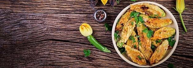 Smażone kwiaty cukinii nadziewane ricottą i zielonymi ziołami. wegańskie jedzenie. kuchnia włoska. transparent.