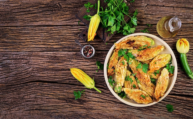 Smażone kwiaty cukinii nadziewane ricottą i zielonymi ziołami. wegańskie jedzenie. kuchnia włoska.