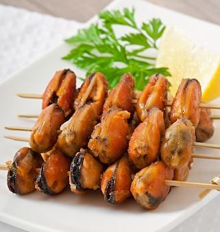 Smażone małże z cebulą na szaszłykach c ozdoby z zielonej fasoli i papryki