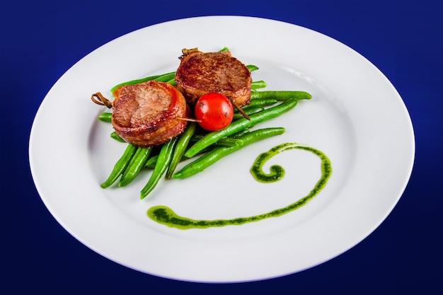 Smażone medaliony wieprzowe na szaszłykach z fasolką szparagową i pomidorem w całości. widok z góry leżał płasko na białym talerzu na niebieskim tle.
