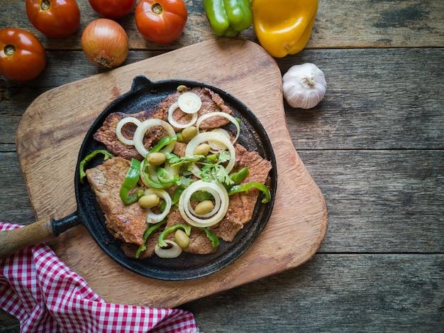 Smażone mięso na żelaznym talerzu z rustykalnym drewnianym stołem flat lay.