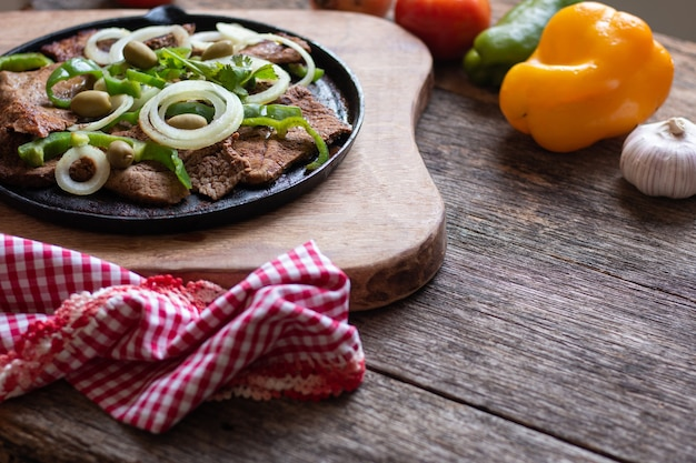 Smażone mięso na żelaznym talerzu z rustykalnym drewnianym stołem.
