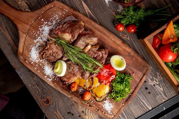 Smażone mięso podawane z grillowanymi warzywami, cebulą i gałązką rozmarynu