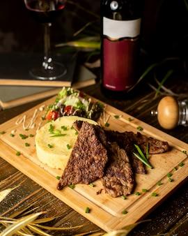 Smażone mięso podawane z puree ziemniaczanym i surówką