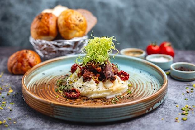 Smażone mięso umieszczone na puree ziemniaczanym doprawionym posiekaną papryką i tymiankiem