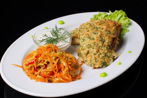 Smażone mięso w bułce tartej z duszoną marchewką i sosem.jedzenie na talerzu. mięso w panierce.