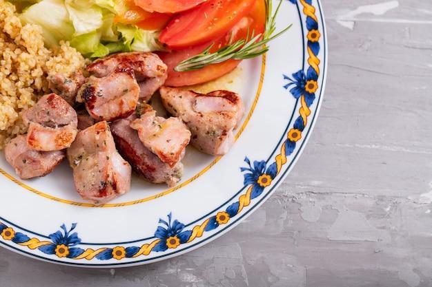 Smażone mięso z komosą ryżową i świeżą sałatą na talerzu na tle ceramicznych