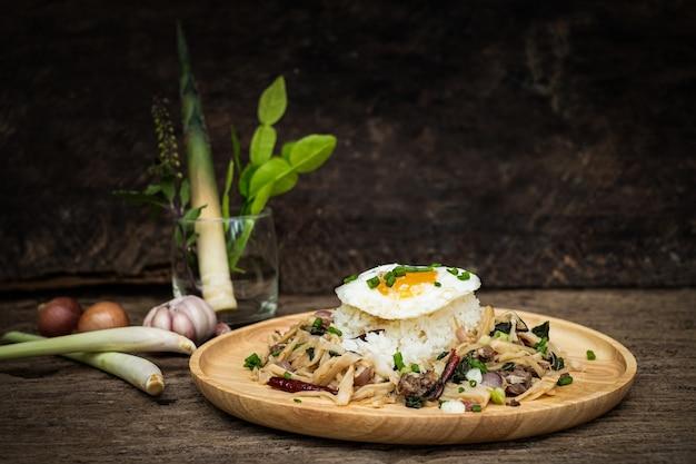 Smażone mięso z pędem bambusa i świętą bazylią podawane z gotowanym na parze ryżowym jajkiem sadzonym