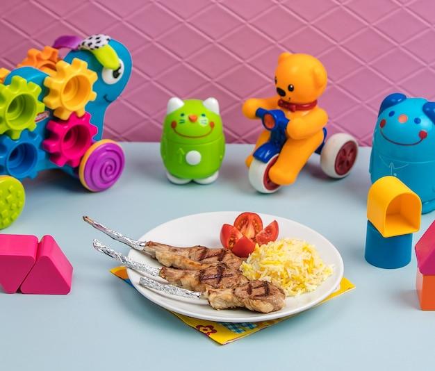 Smażone mięso z ryżem i pomidorem w otoczeniu zabawek
