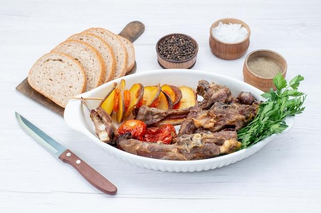 Smażone mięso z zieleniną i pieczonymi śliwkami wewnątrz talerza z bochenkami chleba na lekkim biurku, posiłek danie mięsne obiad warzywny