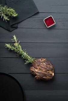 Smażone mięso z zieleniną, sosem i sosem na czarnym drewnianym tle