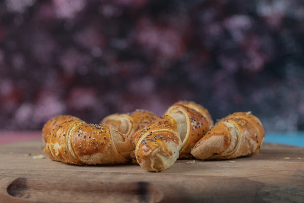 Smażone mini ciasteczka croissant na drewnianej desce.