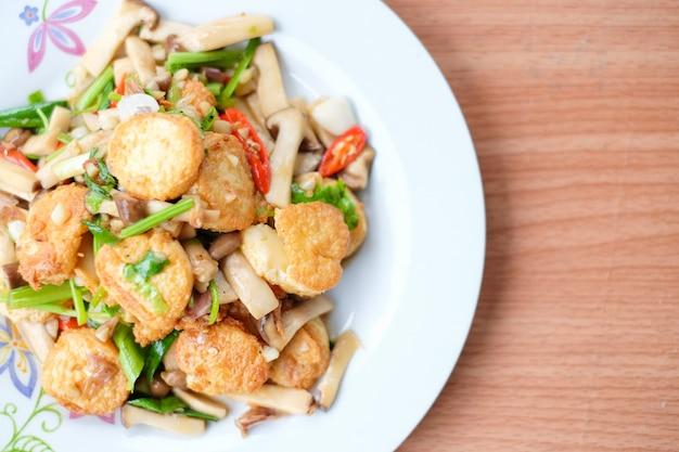 Smażone na gorąco tofu, wieprzowina i pieczarka z sosem z czarnej fasoli serwują na białym naczyniu ustawionym na brązowym stole - domowe jedzenie.