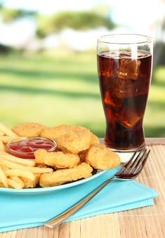 Smażone nuggetsy z kurczaka z frytkami, colą i sosem na stole w parku