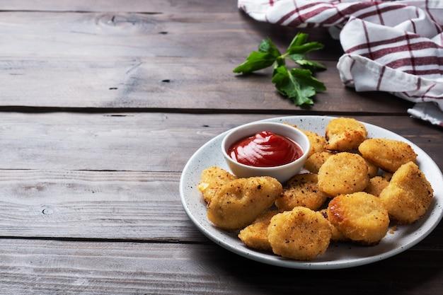 Smażone nuggetsy z kurczaka z sosem pomidorowo-keczupowym.